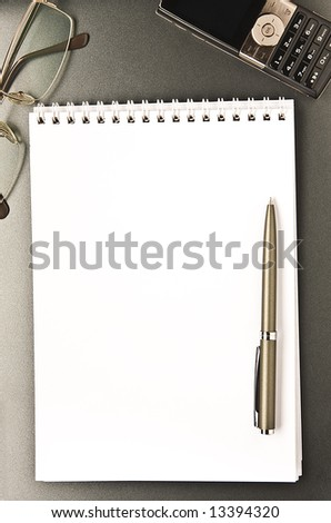 The notebook and cellular phone with the pen lays on a grey background - stock photo