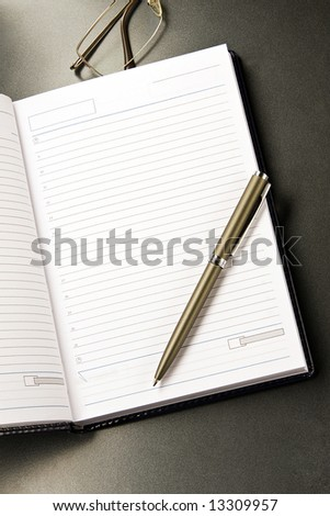 The notebook and glasses with the pen lays on a grey background