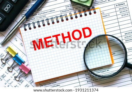 The notebook with the text Method lies on the financial tables with a calculator a magnifying glass a compass and paper clips. Financial concept Stockfoto ©