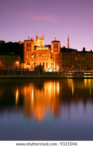 The Notre Dame de Fourviere basilica and the St. Jean cathedral both illuminated and reflected on the waters of the river Saone, in Lyon, France