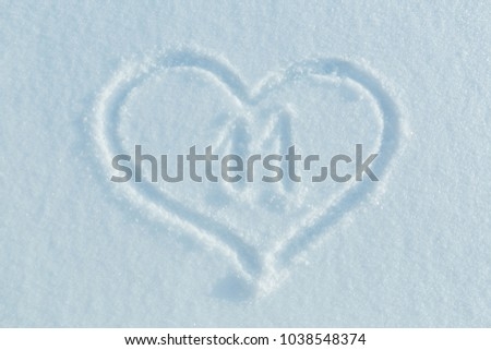 The number eleven drawn on the snow surrounded by a frame in the form of a heart.  #1038548374