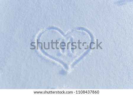 The number eleven  drawn on the snow surrounded by a frame in the form of a heart. #1108437860