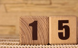 The number fifteen on a wooden cube on a beige background. Cube on a bamboo Mat.