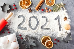 The number 2021 is drawn on flour. The concept of eve 2021, making Christmas cookies.