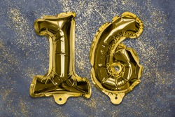 The number of the balloon made of golden foil, the number sixteen on a gray background with sequins. Birthday greeting card with inscription 16. Top view. Numerical digit, Celebration event, template.