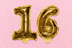 The number of the balloon made of golden foil, the number sixteen on a pink background with sequins. Birthday greeting card with inscription 16. Top view. Numerical digit, Celebration event, template.