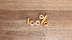 The number one hundred and the percent sign consist of bread dryers laid out on a wooden table.