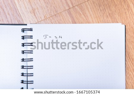 The number pi is written in a notebook with a pen. Pi day number concept. pi is 3.14