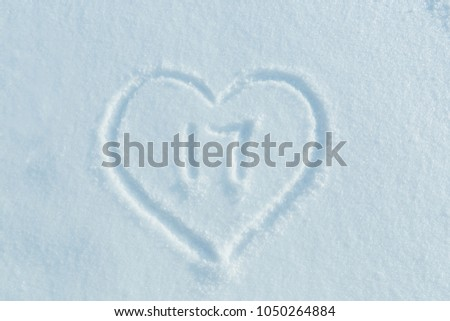 The number seventeen drawn on the snow surrounded by a frame in the form of a heart. #1050264884