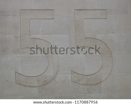 The Number 55 Subtly Etched In A Pale Beige Light Stone Block Wall Of A Building In The United Kingdom #1170887956