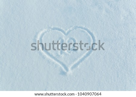 The number twelve drawn on the snow surrounded by a frame in the form of a heart.  #1040907064
