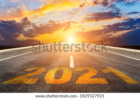 The 2021 numbers are written on a straight highway at sunset (sunrise). Stock photo ©