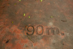 the numbers on the dirty concrete floor. No. 90 m.