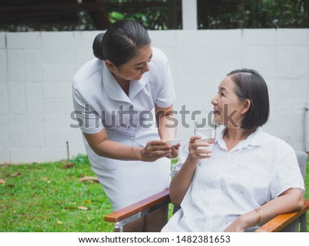 The nurse is caring for the elderly with happiness,elder woman eat drug with water