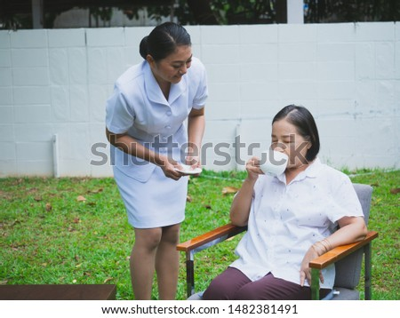 The nurse is caring for the elderly with happiness,Women allow the elder to drink coffee in the morning
