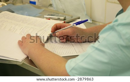 The nurse sits at a table and writes down the information in magazine