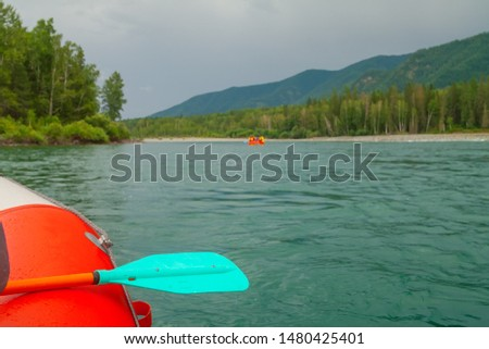 The oar lies on the side of the raft. A large boat and paddle are floating on the river. Mountain river and river rafting.