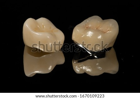 The occlusal surface and margin comparison between full zirconia crown and a metal ceramic/porcelain jacket dental crown with a dark background and reflection Stockfoto ©
