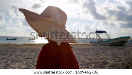 The ocean breeze blows gently as a young woman enjoys a beautiful sunset while on the beach, happy and content wearing a beach hat