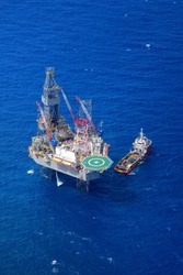 The offshore drilling oil rig and supply boat top view from aircraft.