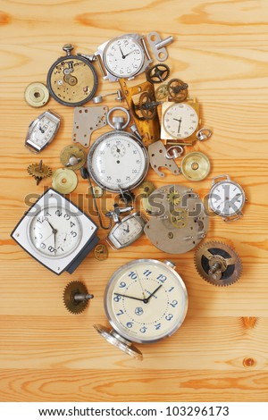 The old alarm clocks, wrist watches, stop watch and clock parts lie on a wooden surface