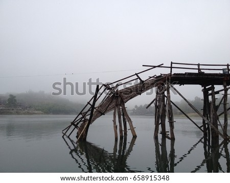 The old and broken wooden bridge over the river in the morning. Travel, tourism, holidays, and construction, inspiration, motivation concept
