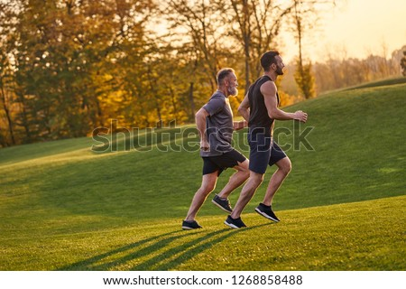 The old and young sportsmen running in the green park
