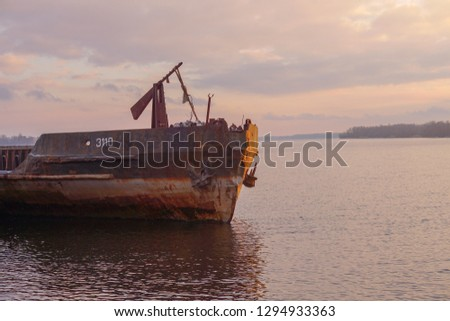 the old barge on the river, the sunset on the river, the old water transport, the stern of the old ship, the rzharaya surface of the water vessel, two barges next to each other