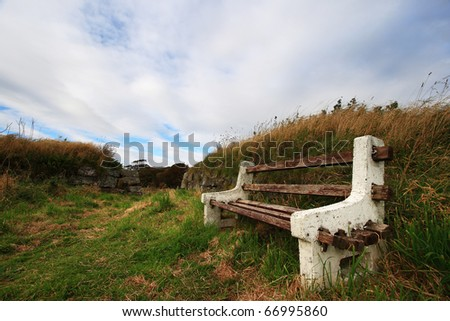The old bench on the grass field, Scotland, UK