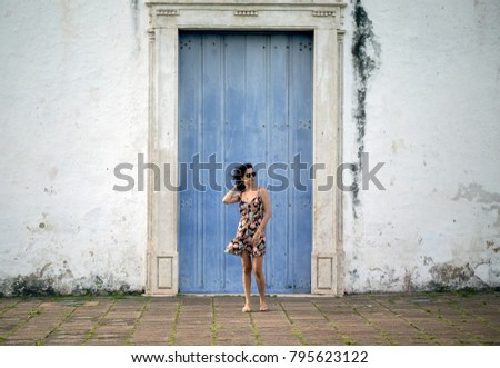 The old blue door and the girl in the printed dress. Hair in the wind. Curly hair.
