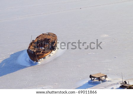 The old boat is frozen into the ice near the old wooden pier