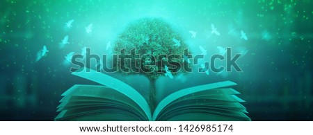 The old book that opened with magic magic, beautiful light, shining in the dark as a blurred background. #1426985174