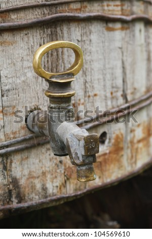 The old brass tap on the wooden cask