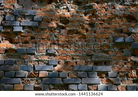 The old brick wall destroyed by the nature and time. The brick wall destroyed by an atmospheric precipitation. Brick wall in many years. #1441136624