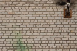 The old brick wall is white. A chimney comes out of the ventilation grate. High quality photo