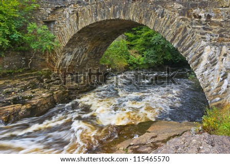 The old Bridge of Dochart, where the River Dochart flows through the village of Killin in the highlands of Scotland, near the area of waterfalls and white water rapids known as the Falls of Dochart.