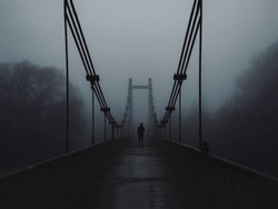 The old bridge over the river in the morning in a heavy fog and the silhouette of a man in the distance. Melancholy, depression or loneliness concept