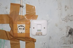 The old broken electrical socket fell off the wall. just repaired with brown duct tape on the walls, dull and dirty white