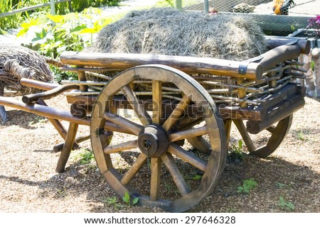 The old cart with hay stands in anticipation of the horse