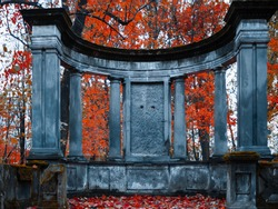The old Catholic cemetery in the fall. Abandoned graves under a layer of fallen leaves. Stone monument with columns on the family burial ground