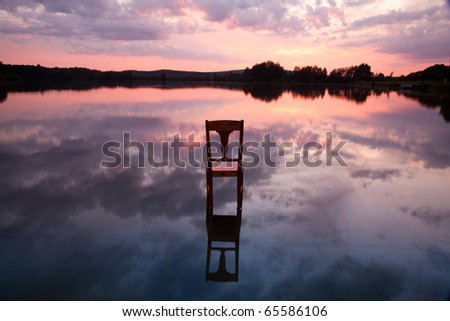 The old chair in the lake at sunset