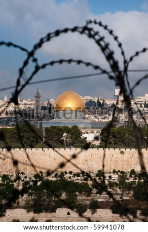The Old City of Jerusalem, including the Dome of the Rock and various church steeples, seen through coils of razor wire, illustrating the Holy Land's history of division and conflict.