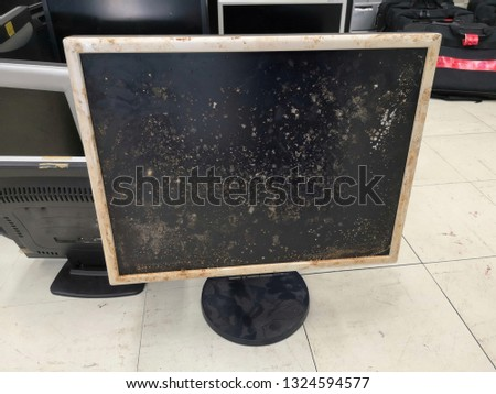 Old computer monitor on old wood table on dark background