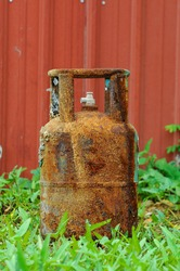 The old cooking gas tank at the side of the tank has a lot of rust attached.