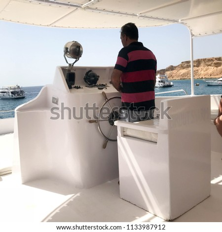 The old dark-skinned Arab captain of the Muslim ship in a red striped shirt controls a ship standing at the helm in the captain's cabin, a boat, a cruise liner in a tropical resort.