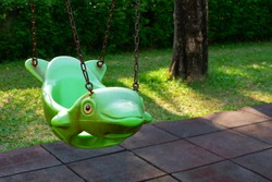 The old empty green hanging swing in dolphin shape and rubber floor tiles with green lawn in outdoor playground area at public park