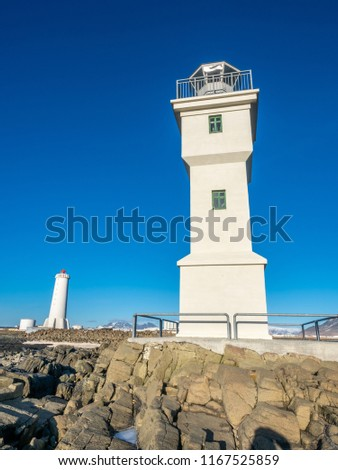 The old inactive Akranes lighthouse at end of peninsula in city, was built since 1918, under blue sky, Iceland