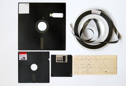 The old 8-inch floppy disk, magnetic tape for an old computer, punched card, a comparison with the flash drive