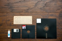 The old 8-inch, 5.25-inch, 3.5-inch floppy disk, punched card for an old ibm computer, a comparison with the USB flash drive