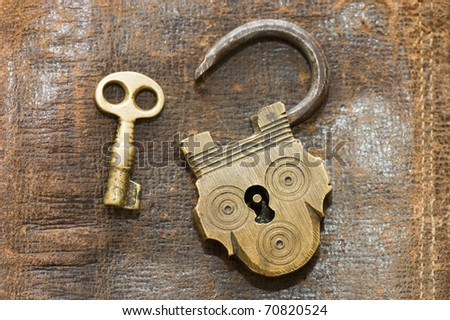 The old lock and key on a leather background